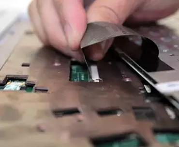 Процесс подключения шлейфа клавиатуры в разъем материнской платы ноутбука