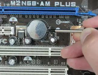 Процесс извлечения батарейки из разъема на материнской плате компьютера